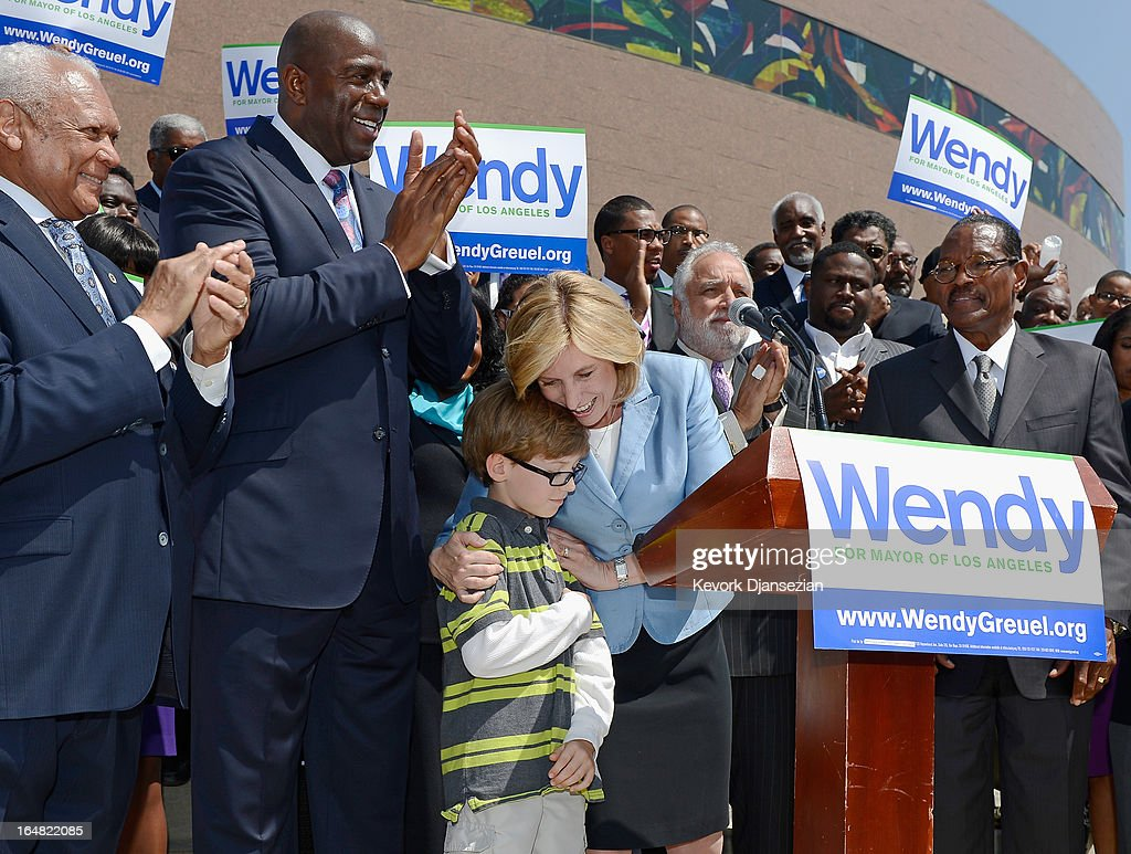 Candidate in the Los Angeles city mayoral race, City Controller Wendy Greuel (C) hugs her son Thomas Schramm, 9, after she received NBA legend and busiessman Earvin 'Magic' Johnson's endorsement during a news conference at the West Angeles Church of God on March 28, 2013 in Los Angeles, California. Garcetti is in a tight race for the May 21 runoff against second-place finisher City Controller Wendy Greuel.