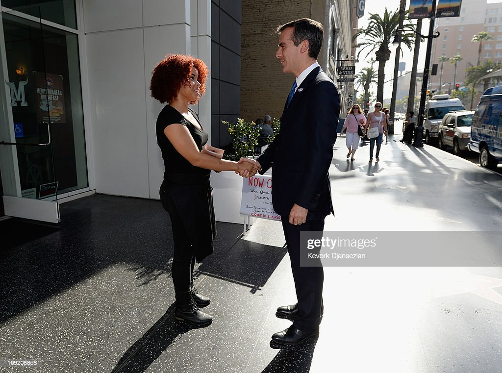 Candidate in the Los Angeles City mayoral race, Councilman Eric Garcetti (R) greets a supporter on Hollywood Boulevard as he campaigns in the closing hours of a run-off election on May 21, 2013 in the Silver Lake area of Los Angeles, California. In what could be a record-low voter turnout, Garcetti is up against Los Angeles City Controller Wendy Greuel for the seat held by two-term Antonio Villaraigosa.