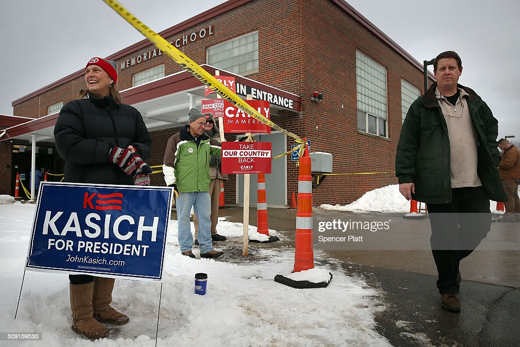 Candidate supporters hold signs outside a middle school serving as a voting station on the day of the New Hampshire Primary on February 9, 2016 in Bow, New Hampshire. After months of campaigning, voters across New Hampshire get to go to the polls today to vote for Democratic and Republican presidential candidates. Following New Hampshire, the race for the presidency moves to South Carolina.