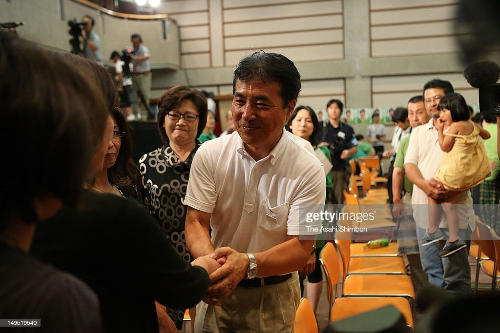 Candidate Tetsunari Iida shakes hands with his supporters after losing to Shigetaro Yamamoto in the Yamaguchi gubernatorial election at his campaign headquarters on July 29, 2012 in Yamaguchi, Japan.