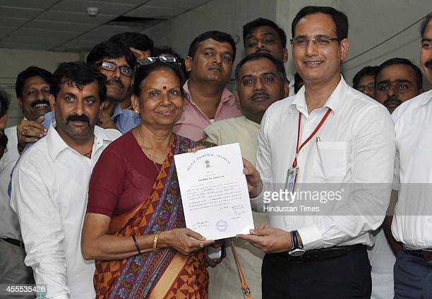 BJP candidate Vimla Batham along with presiding officer pose with her election certificate after winning the Noida assembly seat at the UP...