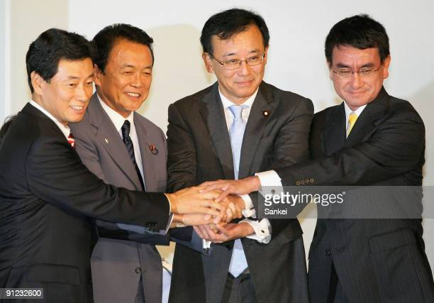 Candidate Yasutoshi Nishimura outgoing President Taro Aso newly elected President Sadakazu Tanigaki and candidate Taro Kono shake hands after...
