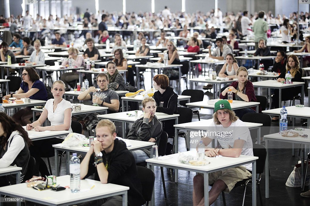 Candidates applying for a place at the Medical University of Vienna sit an exam in a hall of the fair grounds in Vienna on July 5, 2013. According to unofficial data, almost 10,000 people are applying for only 700 places available. AFP PHOTO / PATRICK DOMINGO