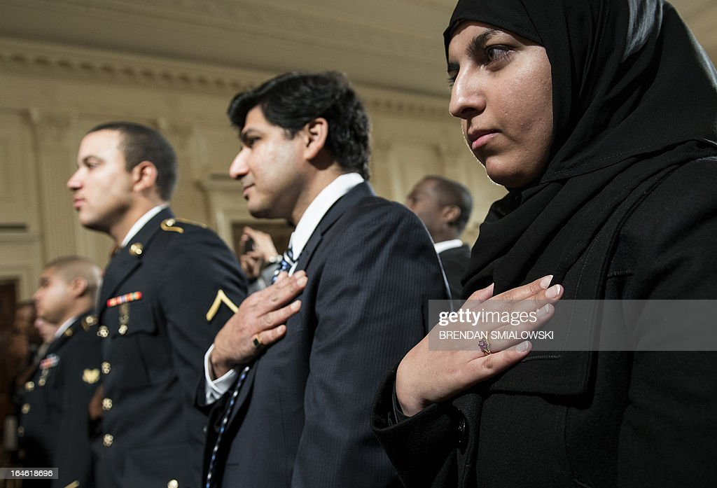 Candidates for citizenship listen the the US national anthem during a naturalization ceremony in the East Room of the White House on March 25, 2013 in Washington. Obama presided while Secretary of Homeland Security Janet Napolitano administered the oath of allegiance to active duty service members and civilians officially granting them United States citizenship. AFP PHOTO/Brendan SMIALOWSKI
