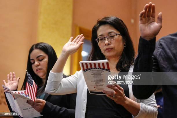 Candidates for US citizenship take the oath of allegiance during a Naturalization Ceremony for new US citizens at the City Hall of Jersey City in New...