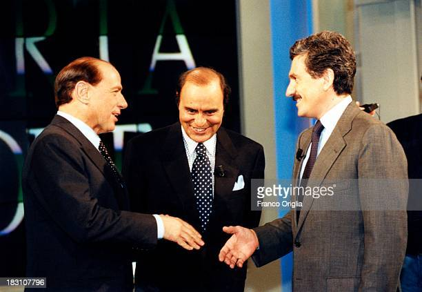 Candidates Prime Minister Silvio Berlusconi and Massimo D'Alema shake hands as presenter Bruno Vespa introduces talk show 'Porta A Porta' on tv...