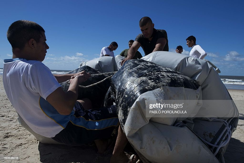 Candidates to the Air Force Academy assemble a pneumatic boat with members of the Uruguayan Air Force Operations, Training and Rescue Unit, at Salinas' beach, near Montevideo, Uruguay on February 27, 2013.AFP PHOTO/Pablo PORCIUNCULA