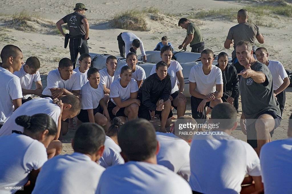 Candidates to the Air Force Academy receive instruction from an instructor before a drill with members of the Uruguayan Air Force Operations, Training and Rescue Unit, at Salinas' beach, near Montevideo, Uruguay, on February 27, 2013.AFP PHOTO/Pablo PORCIUNCULA