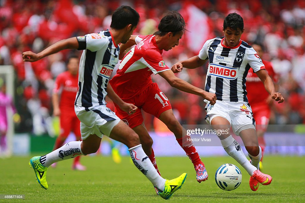 Candido Ramirez and Severo Meza of Monterrey struggles for the ball with Lucas Lobos of Toluca during a match between Toluca and Monterrey as part of...