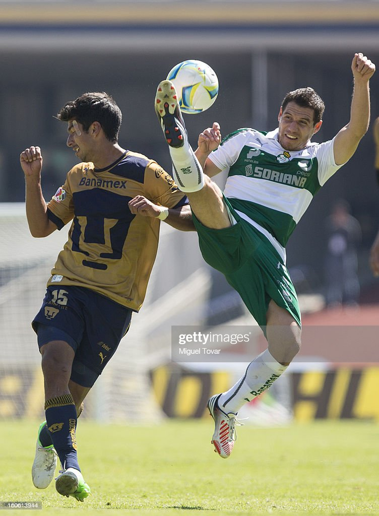 Candido Ramirez (R) of Santos struggles for the ball with Eduardo Herrera (L) of Pumas during a match between Pumas and Santos as part of the Clausura 2013 at Olímpico Stadium on February 03, 2013 in Mexico City, Mexico.