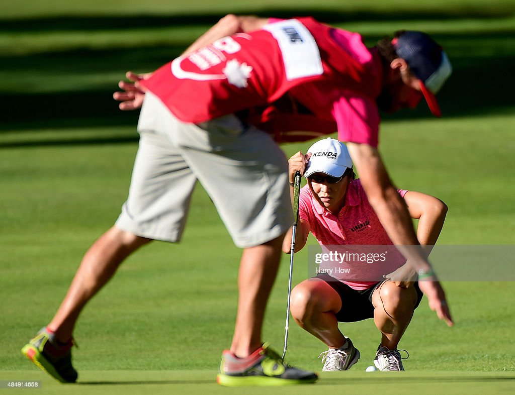 Candie Kung and caddie line up a putt on the 15th green during the third round of the Canadian Pacific Women's Open at the Vancouver Golf Club on August 22, 2015 in Vancouver, Canada.
