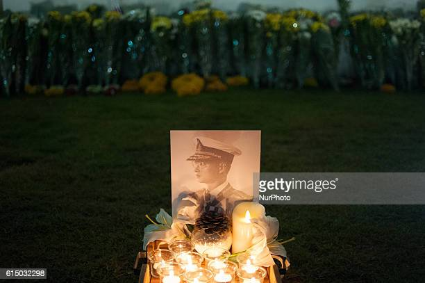 A candle and flowers adorn an image of the late Thai King Bhumibol Adulyadej on the outer wall of the Grand Palace on October 16 2016 Thailand's King...