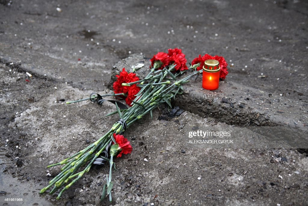 A candle and flowers are layed at a bus stop where 13 people were killed in a trolleybus shelling in Donetsk eastern Ukraine on January 22 2015 At...
