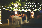 A string of fairy lights and a chandelier with candle hanging in-between trees photographed shining at night with image focus technique focus on the foreground bokeh background and dark and a table wi
