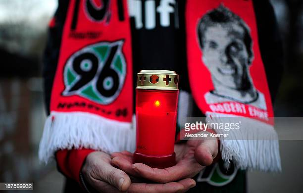 A candle is being held by a fan of German Bundesliga soccer club Hannover 96 in front of HDI Arena on the fourth anniversary of the death of the...