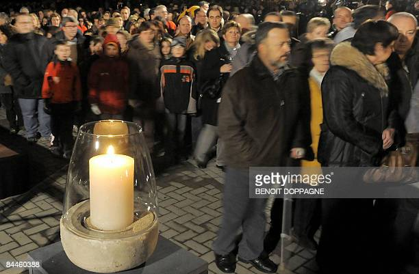 A candle is burning as people gather to commemorate the victims of a knife attack at a Belgian creche last week in Dendermonde on January 26 2009 In...