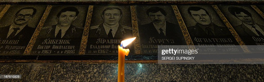 A candle is in front of portraits at the monument to Chernobyl victims in Slavutich, some 50 kilometres (30 miles) from the accident site, and where many of the power station's personnel used to live, during a memorial ceremony early on April 26, 2013. Ukraine on April 26 marks the 27th anniversary of the Chernobyl disaster which was the world's worst nuclear accident.