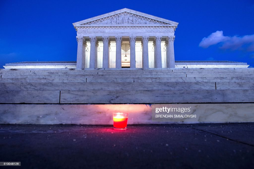A candle is seen at the steps of the US Supreme Court February 13, 2016 in Washington, DC, following the announcement of the death of Supreme Court Justice Antonin Scalia. Scalia, a fiery conservative who helped shape American legal thought, was first appointed to the highest court in the land in 1986 by President Ronald Reagan, making him the first Italian-American to serve there. Scalia was 79. / AFP / Brendan Smialowski