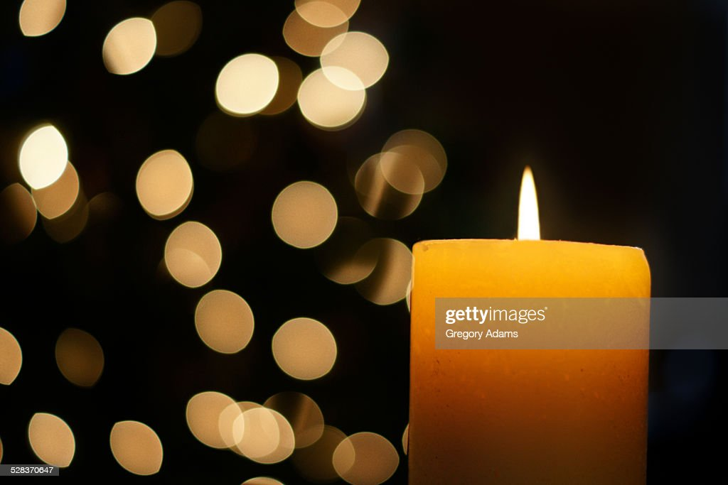 A candle with out of focus light in the background