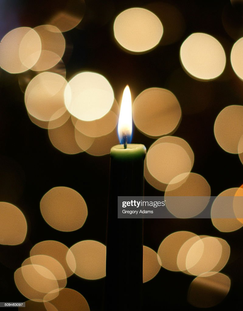 A candle with out of focus lights in background