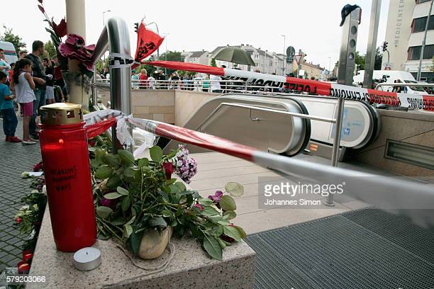 A candle with the words 'Warum Pourquoi Why' written on it is placed nest to a cordoned off area outside the OEZ shopping center the day after a...