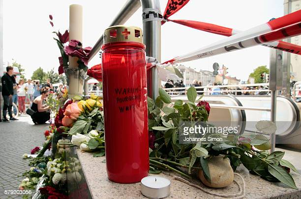 A candle with the words 'Warum Pourquoi Why' written on it is placed outside the OEZ shopping center the day after a shooting spree left nine victims...