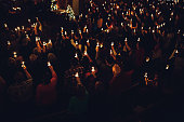 A large group of people in a church congregation hold lighted candles aloft during a time of celebration on the eve of Christmas day, the final day of advent.