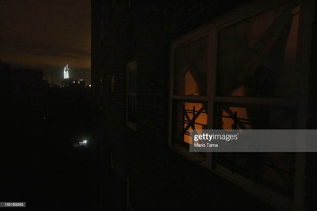 Candlelight glows through the window of an apartment without power in the Jacob Riis housing projects in Manhattan's East Village in front of the shining One World Trade Center (L) on November 1, 2012 in New York, United States. Residents of the housing project have received virtually no governmental assistance since the storm struck. Residents of all the East Village housing projects have been without power and many without water since Superstorm Sandy hit, which flooded some of the housing projects.