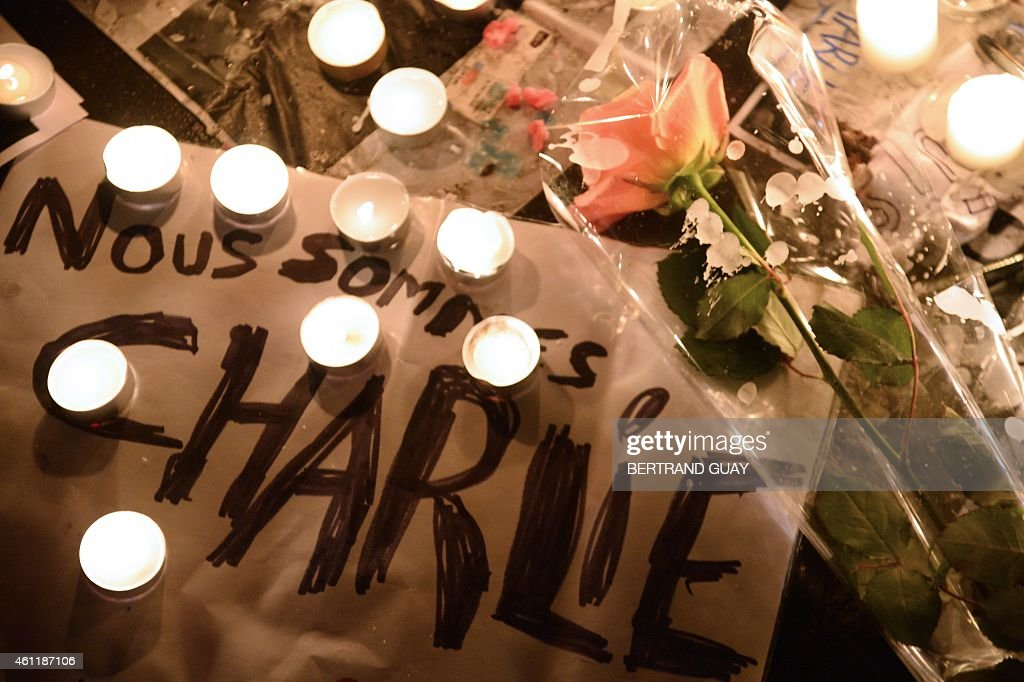 Candles and a flower are placed on a placard reading in French 'We are Charlie' on January 8 on the Place de Republique in Paris during a gathering...