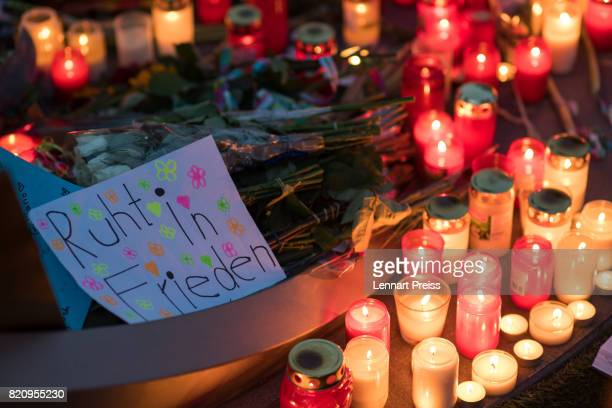Candles and a sign reading 'Ruht in Frieden' are seen at a memorial to commemorate the victims of the shooting spree that one year ago left ten...