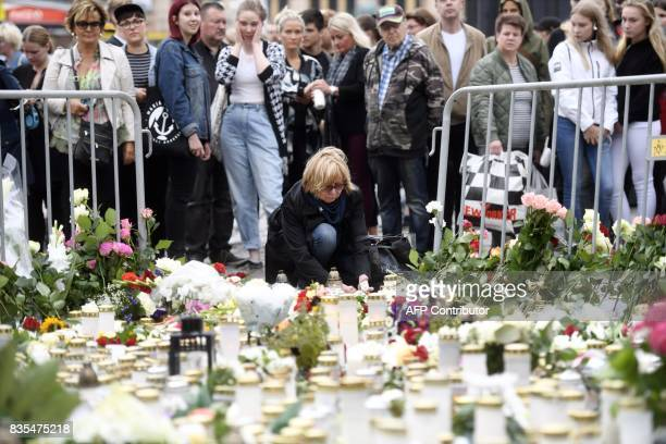 Candles and flowers are left at the makeshift memorial by well wishers for the victims of Friday's stabbings at the Turku Market Square Finland on...