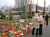 Candles and flowers are pictured in front of the Albertville School Centre on March 13 2009 in Winnenden near Stuttgart Germany The poster reads 'Why...