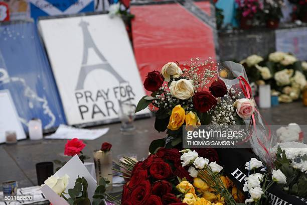 Candles and flowers are placed at a makeshift memorial in Place de la Republique square in Paris on December 13 a month after the Paris terror...