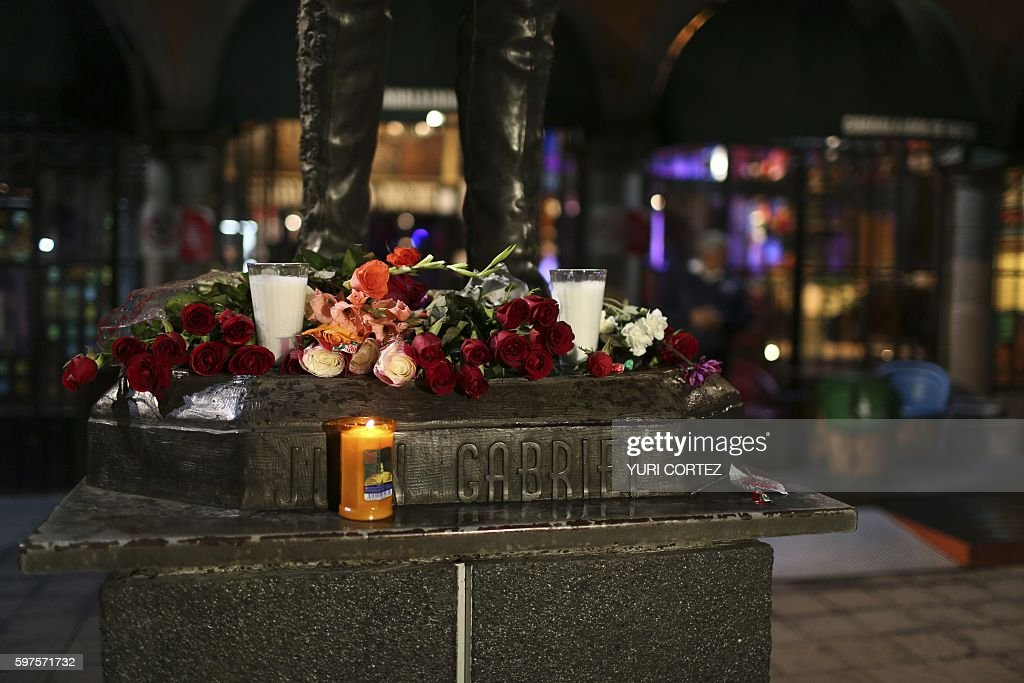 Candles and flowers are placed before the statue of Mexican singer and composer 'Juan Gabriel' at the Plaza Garibaldi on August 28 2016 in Mexico...