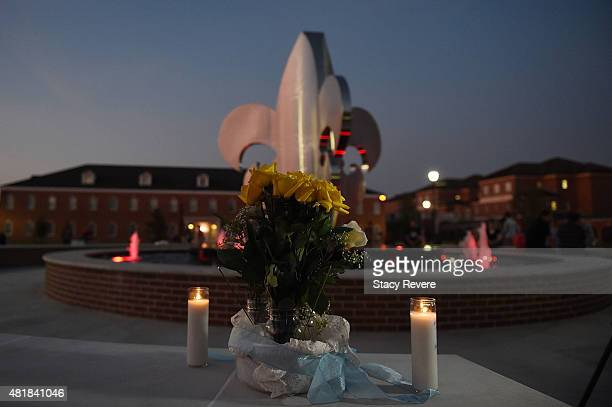 Candles and flowers are placed next to a fountain for a candlelight vigil on the Louisiana Lafayette campus on July 24 2015 in Lafayette Louisiana...