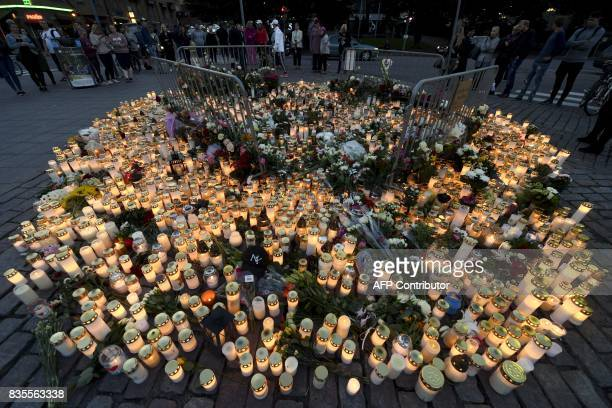Candles and flowers have been left at the makeshift memorial for the victims of Friday's stabbings at the Turku Market Square Finland on August 19...