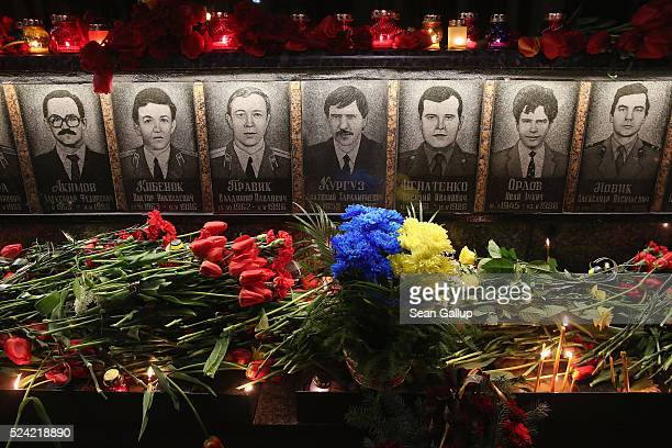 Candles and flowers left by people commemorating the 30th anniversary of the Chernobyl nuclear disaster lie at a memorial to 27 men and three women...