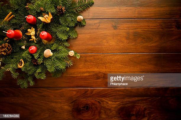 Candles and ornaments on Christmas leaves on wooden floors