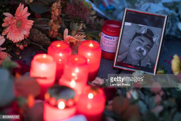 Candles and photographs are seen at a memorial to commemorate the victims of the shooting spree that one year ago left ten people dead including the...