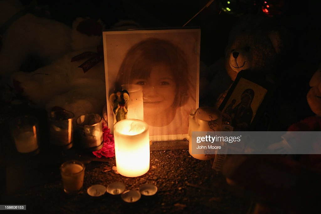 Candles and photos adorn a streetside memorial on December 20, 2012 in Newtown, Connecticut. Six funeral services were held Thursday in the Newtown area for students and teachers slain in the attack.