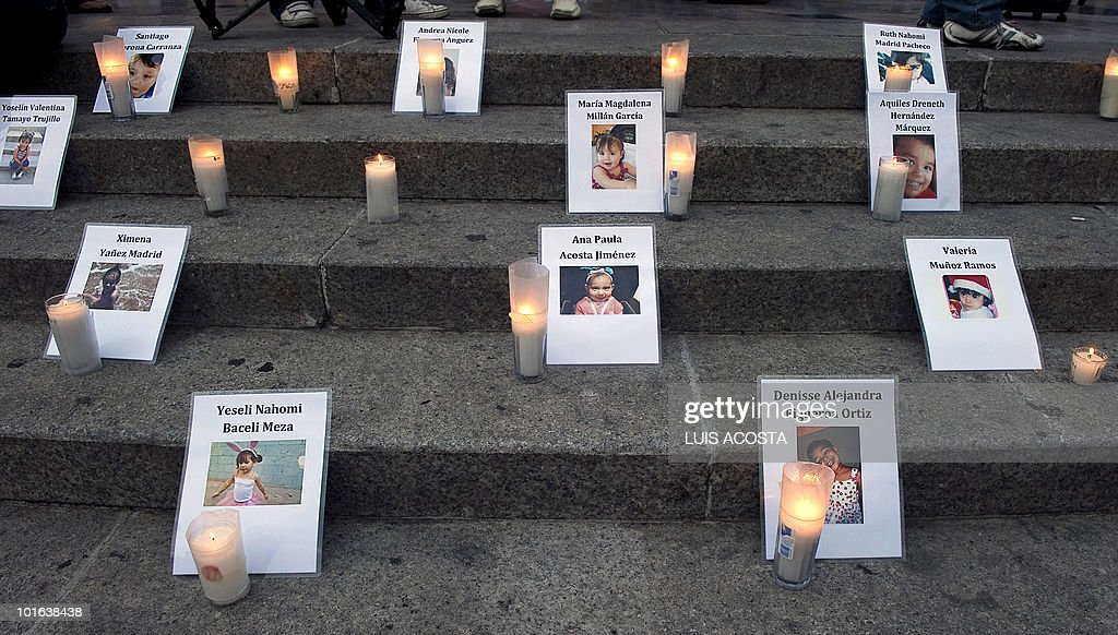 Candles are lit alongside images of victims of a day care center fire at the Independence Angel Monument during a protest in Mexico City on June 4, 2010. Relatives of 49 children killed in a fire at a day care a year ago in Hermosillo, Mexico, demanded that officials - who failed to ensure the center's safety - be brought to justice. AFP PHOTO/Luis Acosta