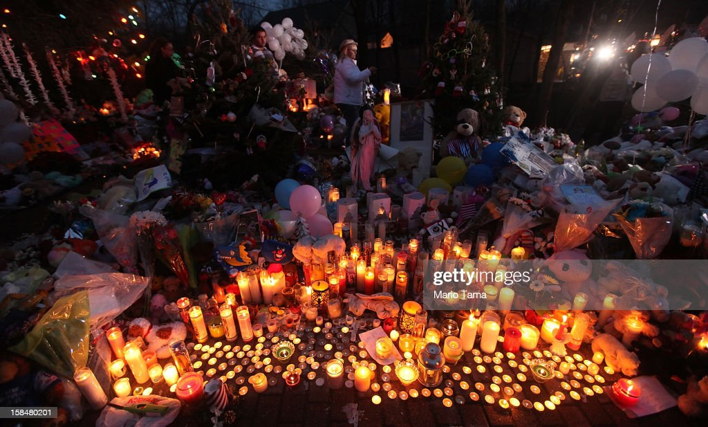 Candles are lit among mementos at a memorial for victims of the mass shooting at Sandy Hook Elementary School, on December 17, 2012 in Newtown, Connecticut. The first two funerals for victims of the shooting were held today.