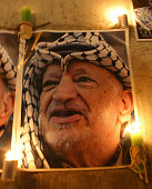 Candles are lit under portraits of late Palestinian leader Yasser Arafat outside the Muqataa Arafat's West Bank headquarters in the city of Ramallah...