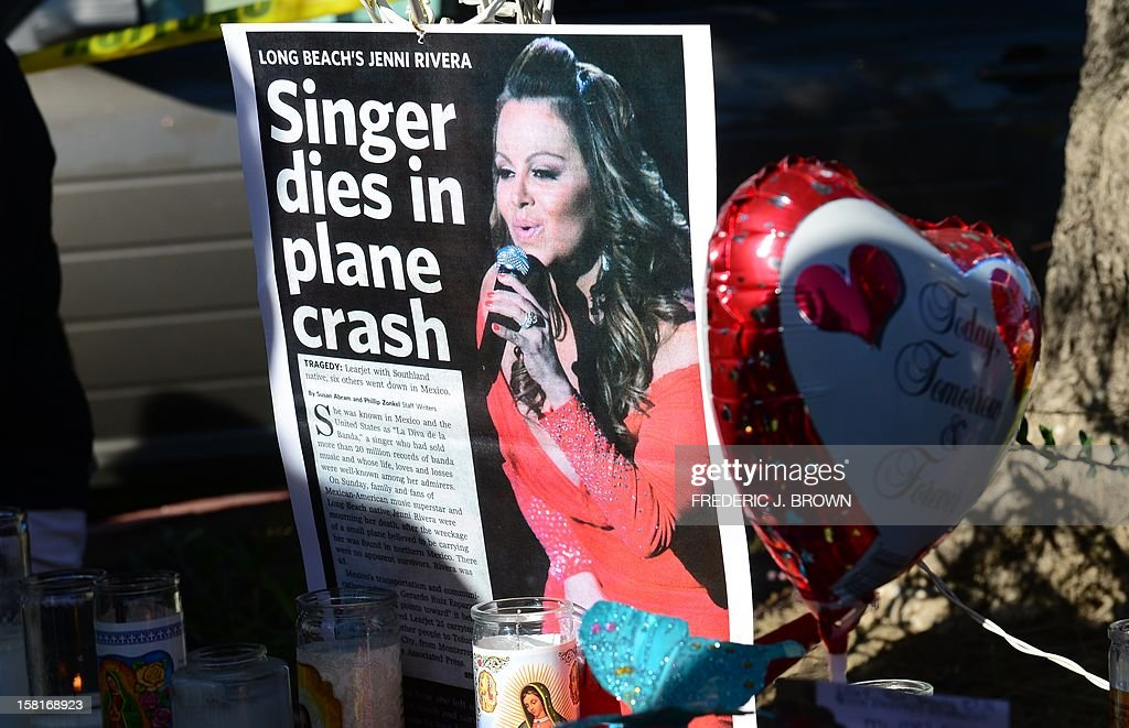 Candles are placed at a makeshift shrine mourning the death of Mexican-American diva Jenni Rivera in front of her home in Lakewood, California on December 10, 2012, south of Los Angeles. Fans and celebrities are mourning the death of Rivera, a star on both sides of the border, as investigators scoured the site of her plane wreck for clues. The 43-year-old singer was among seven people, including two pilots, killed when their small Learjet plane crashed in rugged terrain in the northern Mexican state of Nuevo Leon early December 9. AFP PHOTO / Frederic J. BROWN