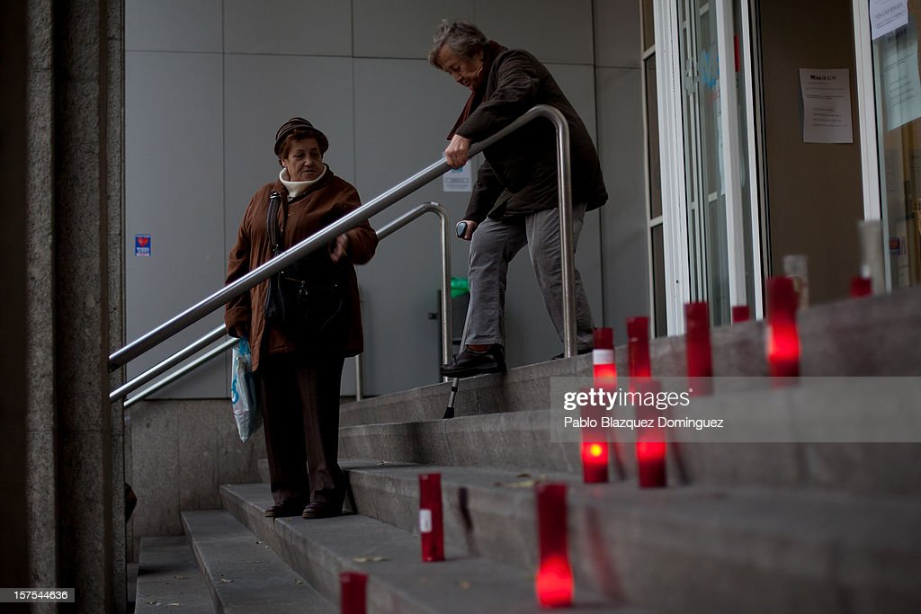 Candles are seen at La Princesa Hospital's stairs while patients walk down on December 4, 2012 in Madrid, Spain. Trade unions called for the second 48-hour health workers' strike in the Madrid region, after the regional government announced severe cuts and privatization of medical centers.