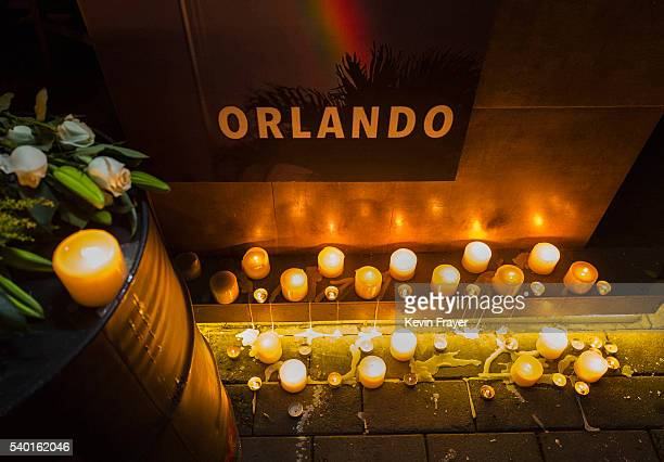 Candles are seen lit under a poster at a memorial vigil for the victims of the mass shooting at the Pulse nightclub at Adam's Bar on June 14 2016 in...