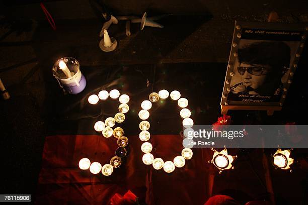 Candles arranged in the shape of the number 30 sit next to a picture of Elvis Presley during a vigil held by fans in memory of the late singer...