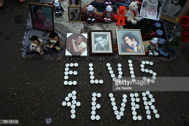 Candles arranged to spell out 'Elvis 4 Ever' sit beside a collection of framed prints of Elvis Presley during a vigil outside the front gates of...