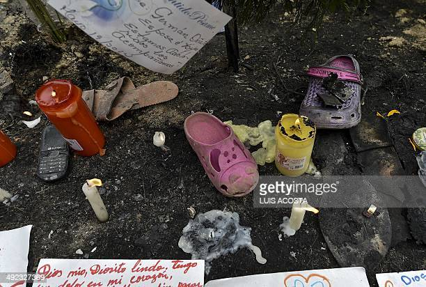 Candles burn next to shoes of the victims who died when a school bus caught fire in Fundacion department of Magdalena Colombia on May 19 2014...