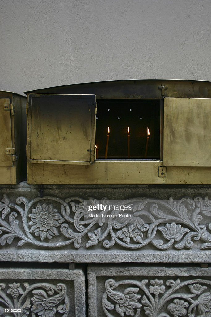 Candles burning in a metal box on an altar : Stock Photo